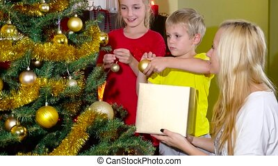 mom with kids decorating christmas tree - mom with kids...