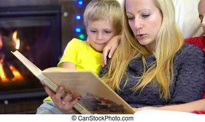 mom and kids reading book at christmas time