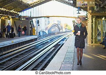 Beautiful young woman waiting for a train in Parisian...