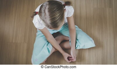Portrait sad little girl sitting on floor at home