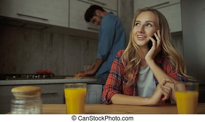 Woman talking on phone, while man preparing food.