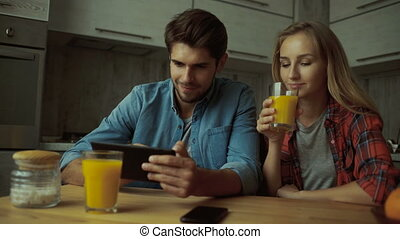 Couple using a digital tablet while having breakfast at home.