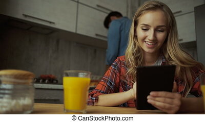 Young lady using tablet, while man preparing food.
