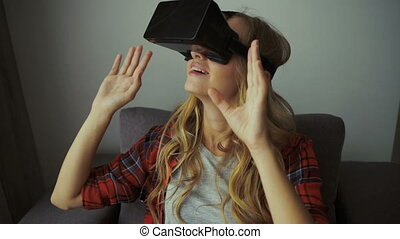 Woman in VR headset looking up at the objects in virtual...