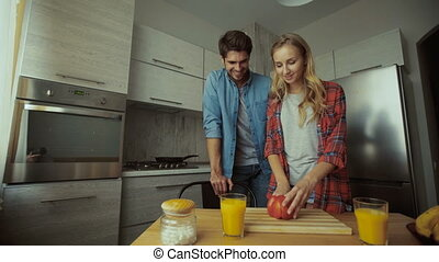 Young lady making breakfast for her man in the kitchen.