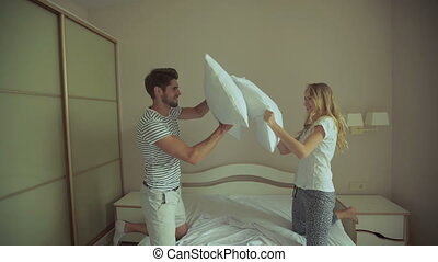 Happy Couple Having Pillow Fight in Hotel Room. They Wear...