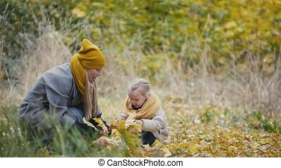 Joyful little daughter with her mommy walks in autumn park -...