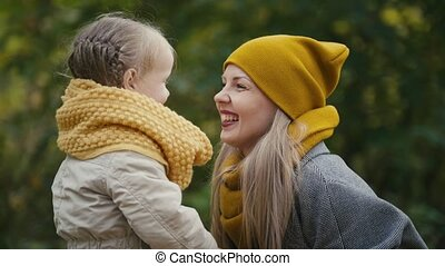 Little blonde girl with her mommy spend time in autumn park...