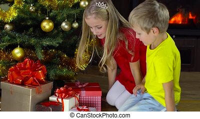 kids open present at christmas time - girl and boy open...