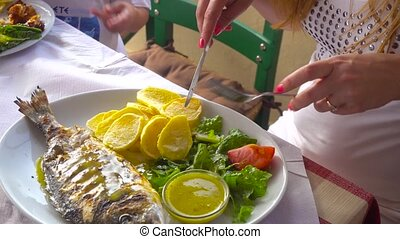 fried fish dorada on plate with potatoes and vegetables -...