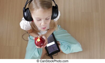 Little girl on the floor in the room using tablet