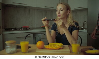 Lady taking pictures of oranges, man looking at her.