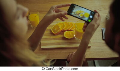 Lady taking pictures of tasty oranges in the kitchen.