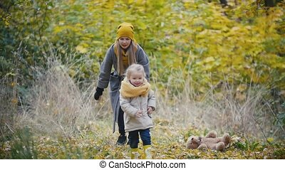 Joyful young girl - little daughter laughs and plays catch-up with the mother in autumn park, slow motion