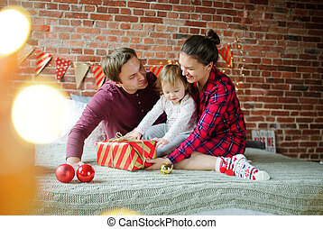 The daddy and mum give daughter the Christmas gift in bright packing