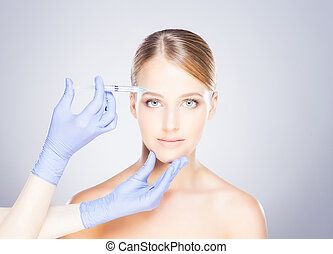 Young blond woman on a face injection procedure - Doctor...