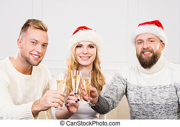 Group of smiling friends in Christmas hats celebrating -...