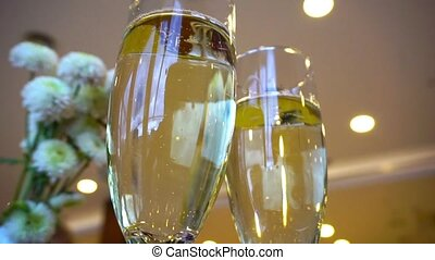 Two glasses of champagne waiting to be served by guests in a...