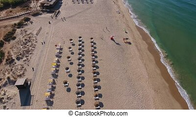 Flight shooting over the beach Falesia with tourists on...