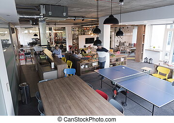 playing ping pong tennis at creative office space - Two...