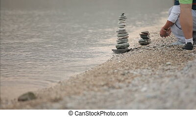 couple making a pyramid of stones on the shore
