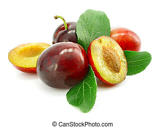 ripe plums with cut and leaf isolated on white background
