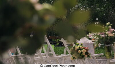 Wedding preparation: creation of rooms for guests outdoor. View through leaves.