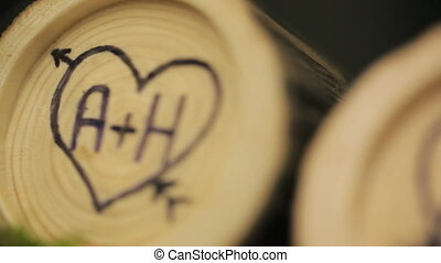 Logs with initials of lovers in heart like wedding decor. In...