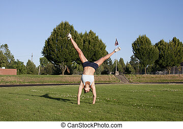 Young and Attractive Female Athlete does a cartwheel. - A...