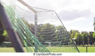 ball flying into football goal net on field - sport, soccer...