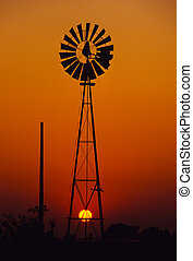 Windmill in Sunset - a windmill is silhouetted against a...