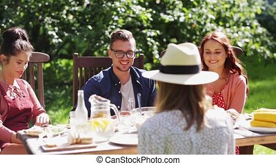 happy friends having dinner at summer garden party -...