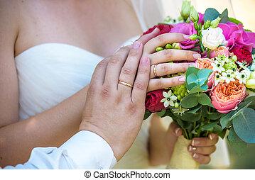 Beautiful wedding bouquet in hands of the bride and groom.