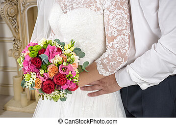 Beautiful wedding bouquet in hands of the bride and groom