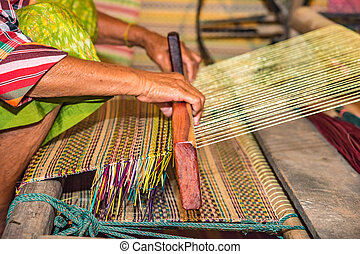 Weaving mats from dry reed - Closeup old woman hands weaving...