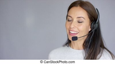 Adorable call center agent speaking with someone on headset...