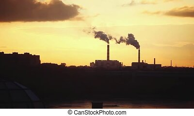 A view of industrial buildings silhouetted against a pinkish...