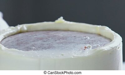 Confectioner decorates the cake and cover it with butter...