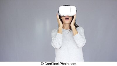 Excited woman watching something on her virtual reality...