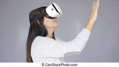 Adorable woman working with virtual reality glasses. She...
