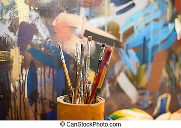 brushes for drawing in a glass against the background of a canvas. brushes for drawing at art school.