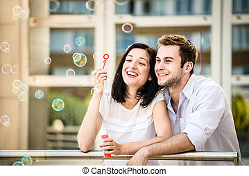 Couple have fun with bubble blower - Young couple have great...