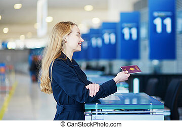 Young woman in international airport at check-in counter,...