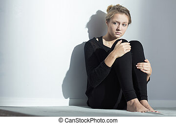 Depressed woman sitting on a floor