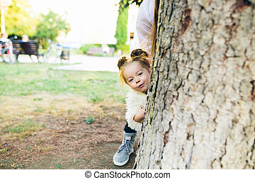 Cute little girl is playing outdoors