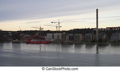 Floating on the river by buildings, tower cranes and red...