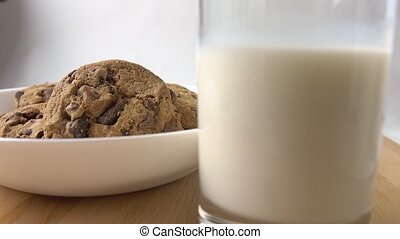 Hands taking chocolate chip cookies and glass of milk for...
