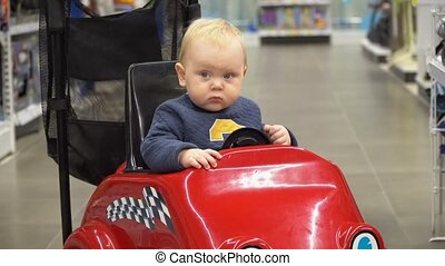 Baby sitting in the shopping cart in a store.