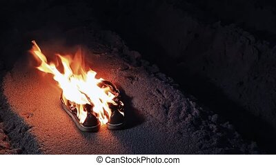 Burning boots on the sand at coast 4k