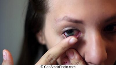 girl inserts lenses - Woman putting on contact lenses at...